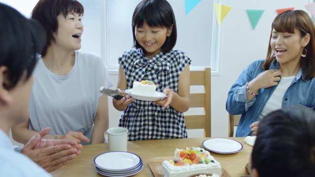 vídeos de stock, filmes e b-roll de menina, distribuindo bolo de aniversário com a família - mesa de jantar