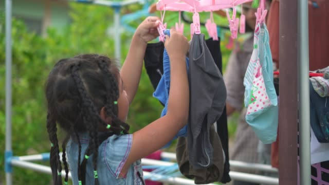 little girl hanging clothes with her grandmother - laundry stock videos & royalty-free footage