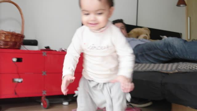 vídeos y material grabado en eventos de stock de little girl happy and barely walking playing with a coloured ball with her dad - planta del pie