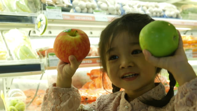 little girl having fun shopping in supermarket - apple fruit stock videos & royalty-free footage