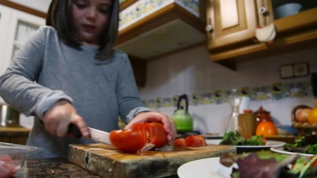 little girl helping at home preparing dinner for the family. - nur mädchen stock-videos und b-roll-filmmaterial