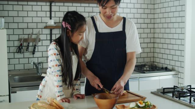 お父さんが昼食を作るのを助ける小さな女の子 - daughter点の映像素材/bロール