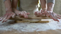 Little girl helping grandmother to roll dough for pizza, family recipe, cooking
