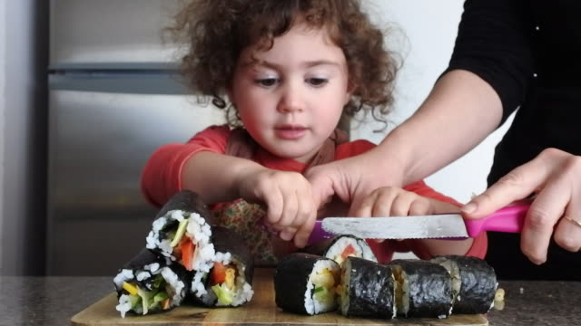 Little girl helps her mother to cut Sushi