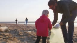 Little girl helps her parents to clean up area of dirty beach with garbage bags