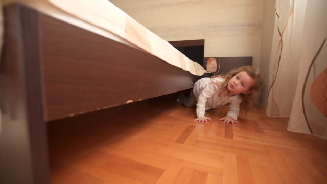 little girl hiding below bed - mischief stock videos & royalty-free footage