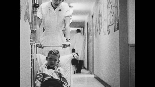 little girl holding a doll on the hospital bed; little girl crying; nurse pushing toddler on small bed down the hallway; baby laying against a pillow - 1950 1959 stock videos & royalty-free footage