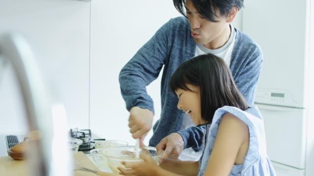 vídeos de stock, filmes e b-roll de menina, segurando a tigela como massa de bolo de pai mexe - família de duas gerações