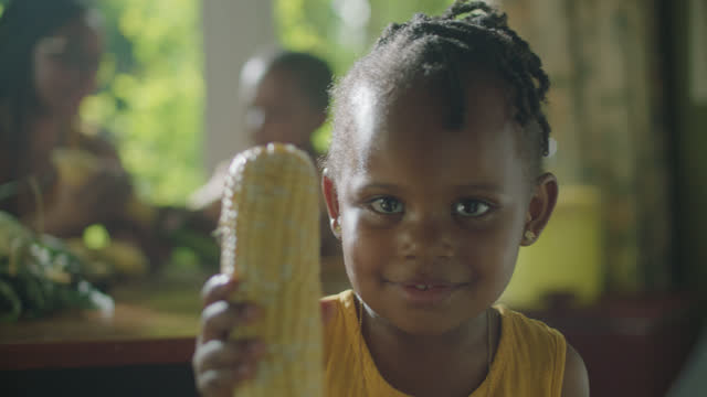 CU of little girl holding corn
