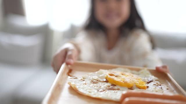 vídeos y material grabado en eventos de stock de niña sosteniendo huevo frito y salchicha en el desayuno - huevos fritos de un solo lado