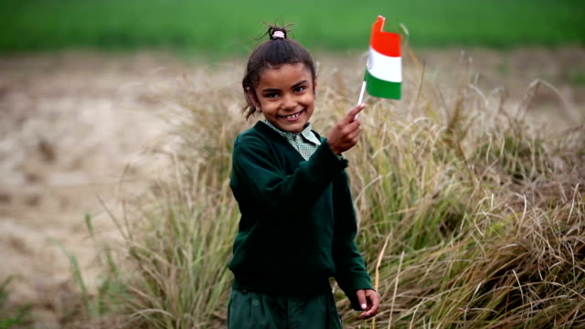 little girl holding indian national flag in the nature - indian flag stock videos & royalty-free footage