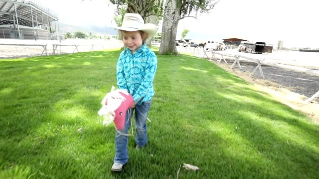 vidéos et rushes de petite fille tenant cheval jouet près d'arène de rodéo - monter à cheval