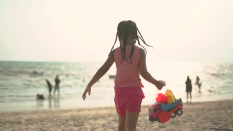 little girl holding toy truck in her hand walking toward seashore - braided hair stock videos & royalty-free footage
