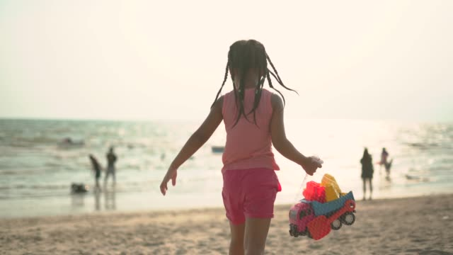 little girl holding toy truck in her hand walking toward seashore - weaving stock videos & royalty-free footage