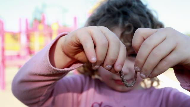vídeos y material grabado en eventos de stock de cu little girl holding worm at playground / toronto, ontario, canada  - gusano