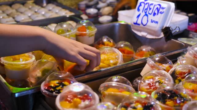 stockvideo's en b-roll-footage met meisje houdt van kleurrijke zoete snoep in de winkel - rommelmarkt