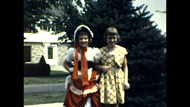 little girl in a red dress and bonnet, another girl in yellow dress standing in front of a pine tree; the two girls walk hand in hand toward camera... - 1940 1949 stock videos & royalty-free footage