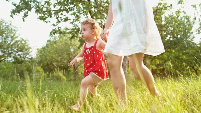 stockvideo's en b-roll-footage met slo mo ts meisje in een rode jurk hand in hand met een jonge vrouw in witte jurk als ze over de weide lopen - witte jurk