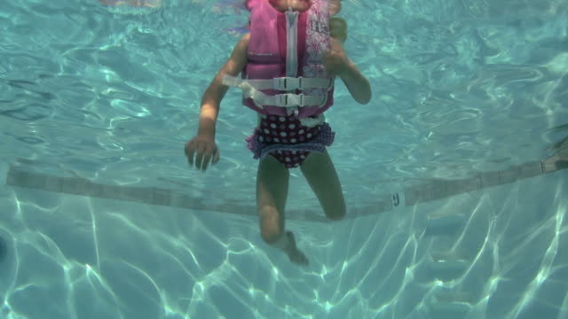 little girl in a swimming pool - verdecktes gesicht stock-videos und b-roll-filmmaterial