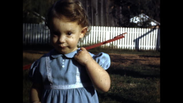 little girl in blue dress walking on the grass, white fence behind her; little girl walks toward camera; close up of her staring at the camera, red... - only girls stock videos & royalty-free footage