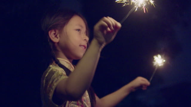 little girl in chinese dress with a sparkler at night. - gold dress stock videos & royalty-free footage