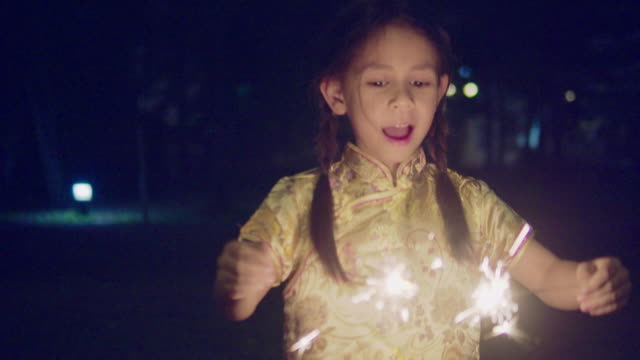 vídeos de stock e filmes b-roll de little girl in chinese dress with a sparkler at night. - cultura tailandesa