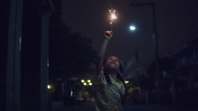 little girl in chinese dress with a sparkler at night. - sparkler stock videos & royalty-free footage