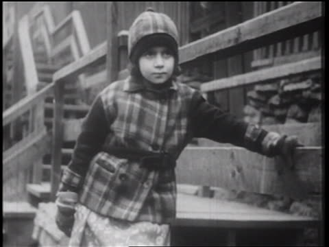 b/w 1939 little girl in coat + hat standing outside by stairway in winter / documentary - woolly hat stock videos and b-roll footage
