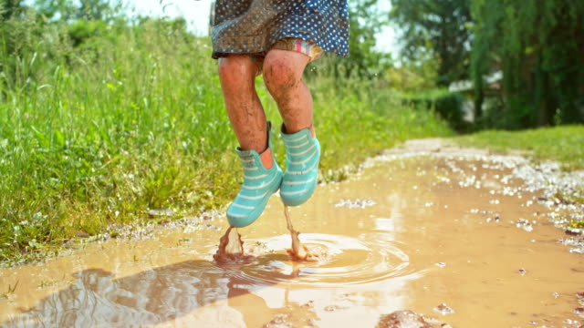 slo mo little girl in dotty dress and rainboots covered in mud from jumping in a muddy puddle - dirt stock videos & royalty-free footage