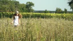 Little girl in hat running through a meadow