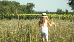Little girl in hat runs through a meadow