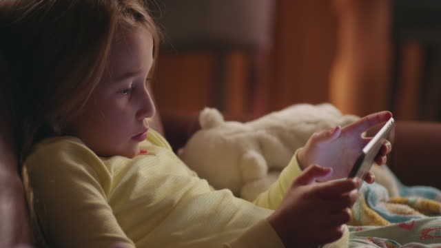 little girl in pajamas lounges cozy on the couch and plays on an ipad; professional mom crosses in the background. - only girls stock videos and b-roll footage