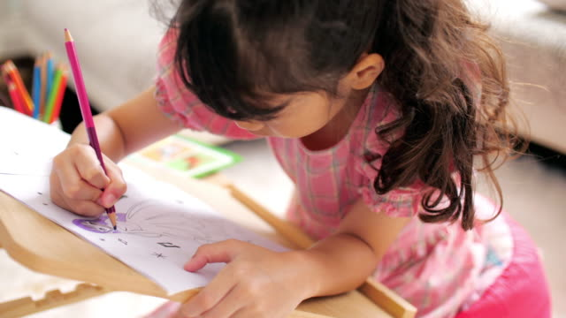 little girl in pink dress drawing and writing on drawing book in living room at home - pencil drawing stock videos & royalty-free footage