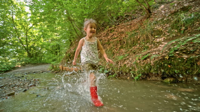 slo mo little girl in red boots running in a creek in the forest - mud stock videos & royalty-free footage