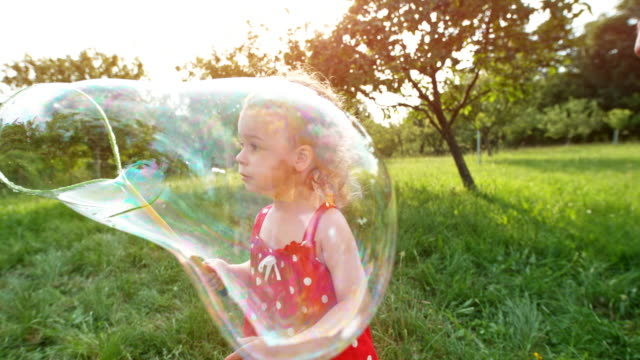 SLO MO Little girl in red dress making huge soap bubbles in the sunny orchard