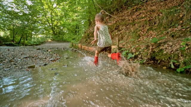 slo mo pov little girl in red rain boot running across a creek in a forest - wellington boot stock videos & royalty-free footage