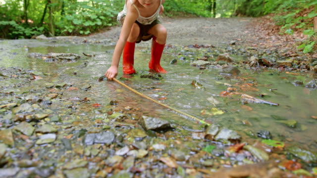 slo mo little girl in red rain boots playing in the forest jumping in a small creek - wellington boot stock videos & royalty-free footage