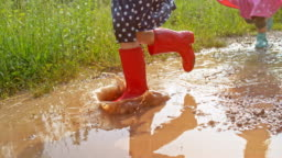 SLO MO Little girl in red rain boots running across a muddy puddle
