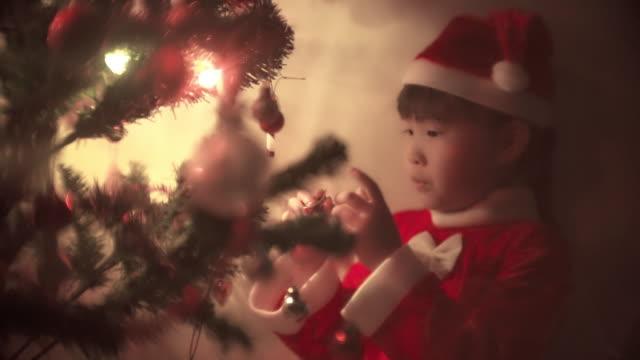 little girl in santa dress decorating christmas tree - calendar date stock videos & royalty-free footage