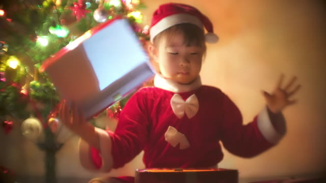 little girl in santa dress opens a gift for christmas - calendar date stock videos & royalty-free footage