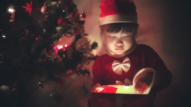 little girl in santa dress opens a gift for christmas - little girls flashing stock videos and b-roll footage