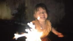 Little girl in thai dress with a sparkler in loi kratong festival
