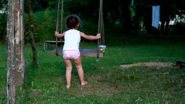 Little girl in underwear playing with a rope swing