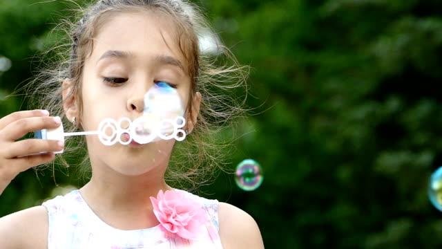 stockvideo's en b-roll-footage met klein meisje in witte jurk blazen van zeepbellen in park-slowmotion - witte jurk