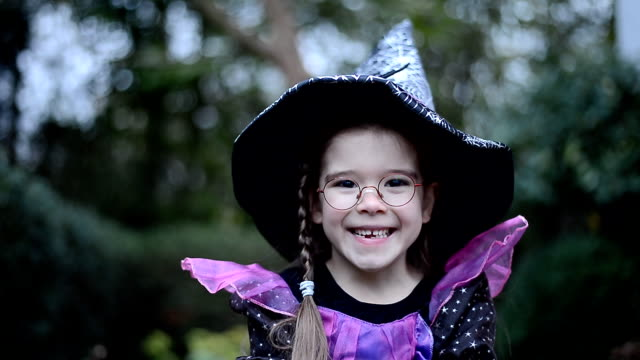 stockvideo's en b-roll-footage met klein meisje in heks kostuum op halloween, close-up - verkleden