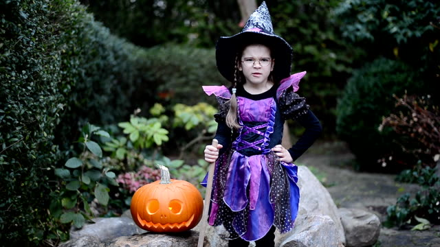 little girl in witch costume dancing around jack o'lantern at halloween - halloween stock videos & royalty-free footage