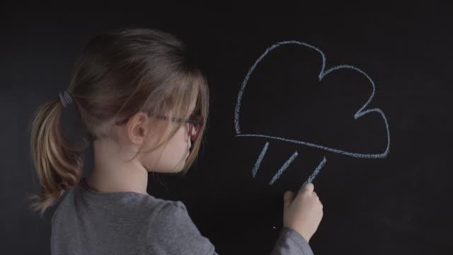 vidéos et rushes de la petite fille dessine le nuage sur le tableau - activité