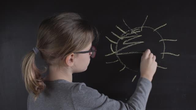 little girl is drawing sun on chalkboard - lavagna video stock e b–roll