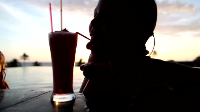 little girl is drinking fruit cocktail near the swimming pool on a tropical island. - tropical cocktail stock videos & royalty-free footage