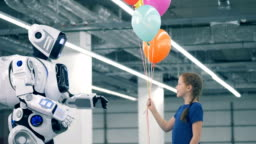 Little girl is giving balloons to a human-like cybord
